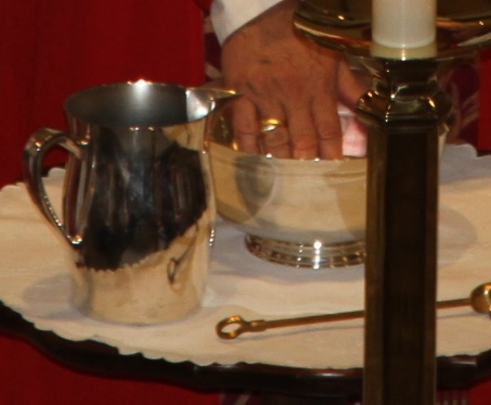 Priest laying hands over Communion wine and bread